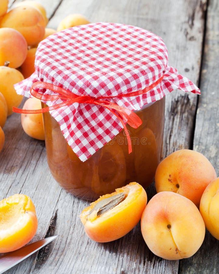 El tarro del atasco y del albaricoque maduro da fruto en la tabla imágenes de archivo libres de regalías