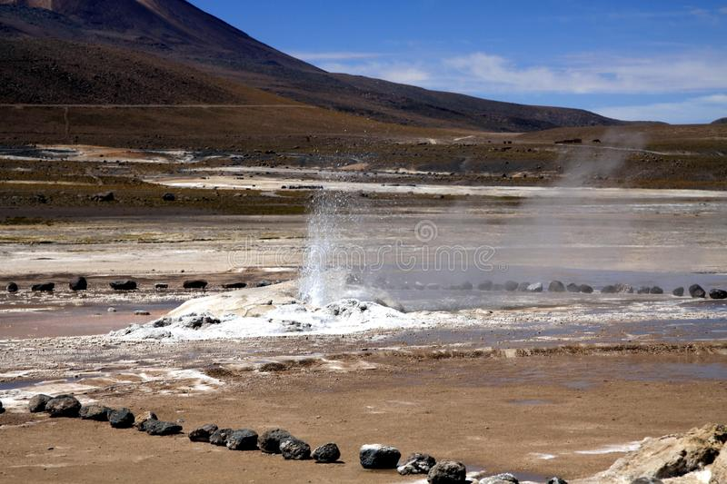 El Tatio geysers in Atacama desert, Chile: Wide geothermal steaming field. Wide geothermal steaming field with mountain under blue sky royalty free stock photography