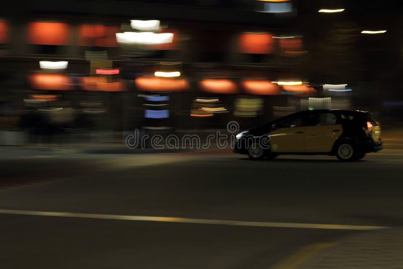 El taxi amarillo móvil está conduciendo en la ciudad de Barcelona de la noche foto de archivo libre de regalías