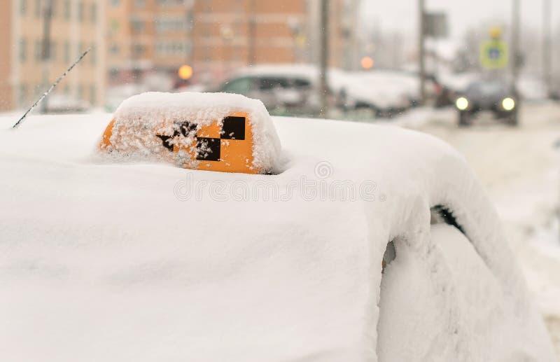 El taxi cubierto con los pasajeros que esperaban de la nieve para parqueó en invierno con un a cuadros en el tejado fotografía de archivo
