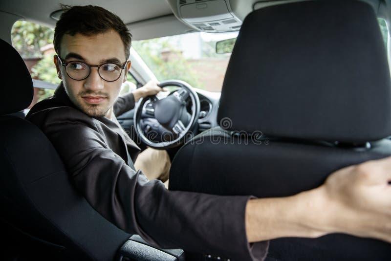El taxista joven mira detrás sobre los asientos Él se está sentando en su coche fotos de archivo
