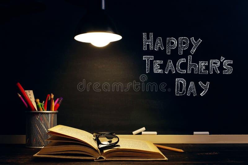 El teacher' escritorio de s o un trabajador, en los cuales los materiales de escritura mienten, libros, por la tarde debajo  fotografía de archivo libre de regalías