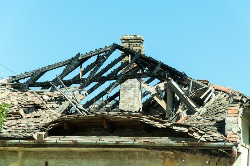El tejado quemado de la casa civil abandonada en Ucrania del este dañó por la explosión de la granada en la zona de guerra imágenes de archivo libres de regalías