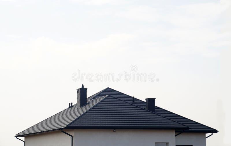 El tejado se hace de las tejas de tejado del metal Una casa residencial nuevamente construida fotos de archivo