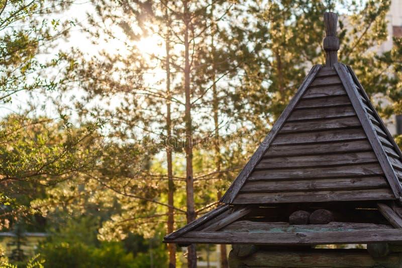 El tejado triangular de una pequeña casa de madera en el verano en la luz de la puesta del sol fotografía de archivo libre de regalías