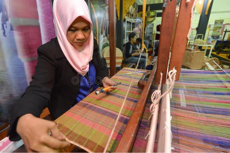 El tejer de la materia textil de Songket foto de archivo