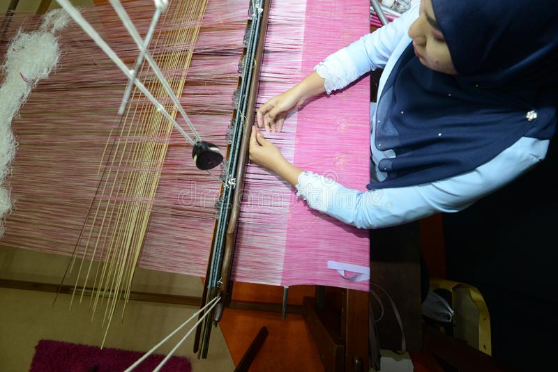 El tejer de Songket foto de archivo