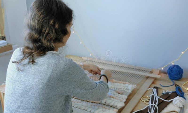 El tejer en un telar Mujer joven que corre en un telar Visión posterior fotografía de archivo libre de regalías