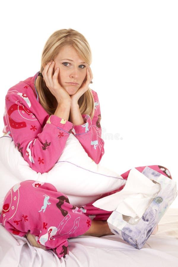 El tejido rosado de los pijamas de la mujer sienta las manos por la cara triste imagenes de archivo