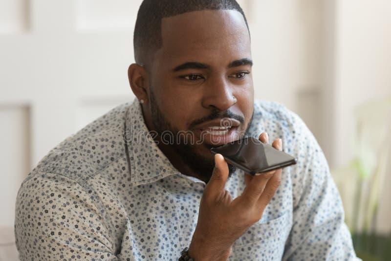El teléfono africano joven de la tenencia del hombre pregunta a ayudante de la voz hace llamada foto de archivo