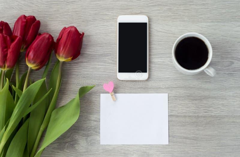 El teléfono blanco con una hoja de papel miente en una tabla de madera blanca con una taza de café y de flores rojas fotos de archivo