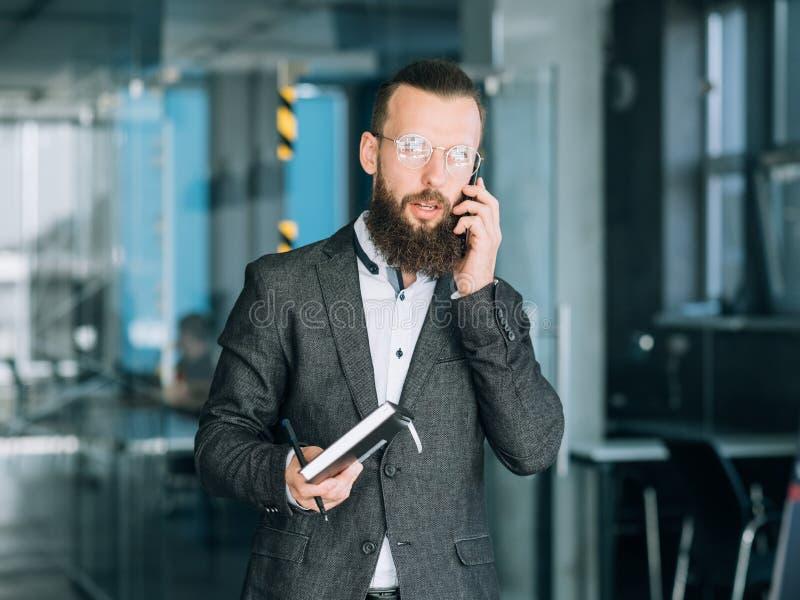 El teléfono de la charla del hombre de negocios piensa memoria de la reflexión imagen de archivo