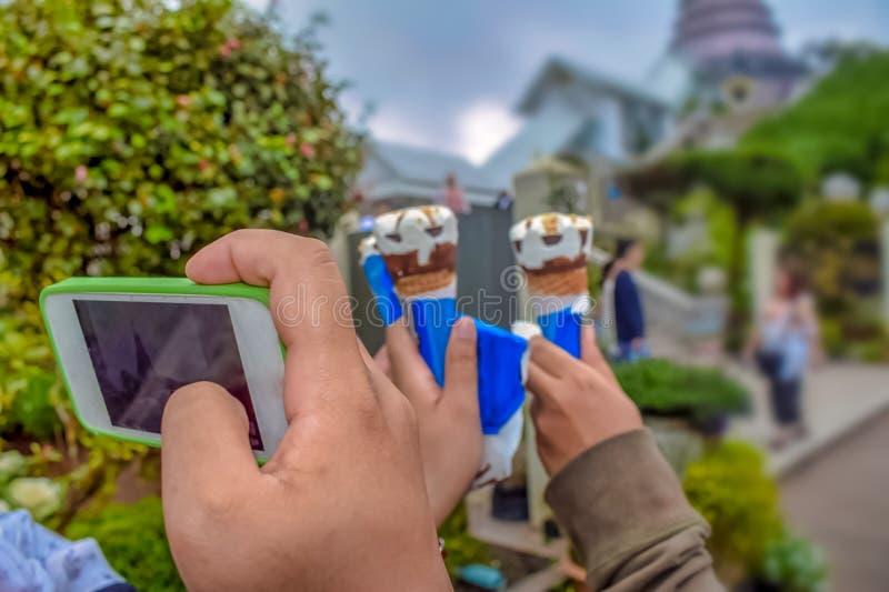 El teléfono de la mano de la tenencia de la mano de la mujer toma una foto fotos de archivo