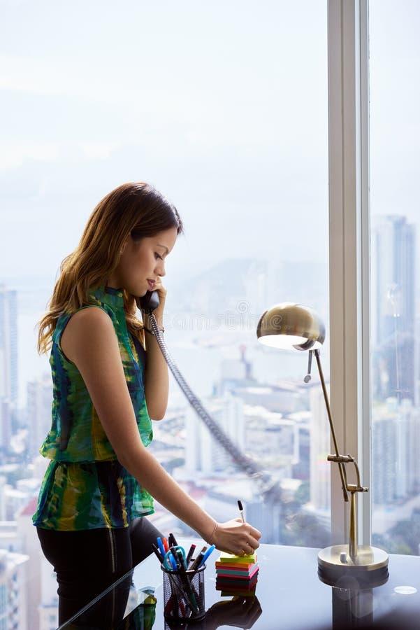 El teléfono de secretaria Woman With Wired escribe la nota pegajosa imágenes de archivo libres de regalías