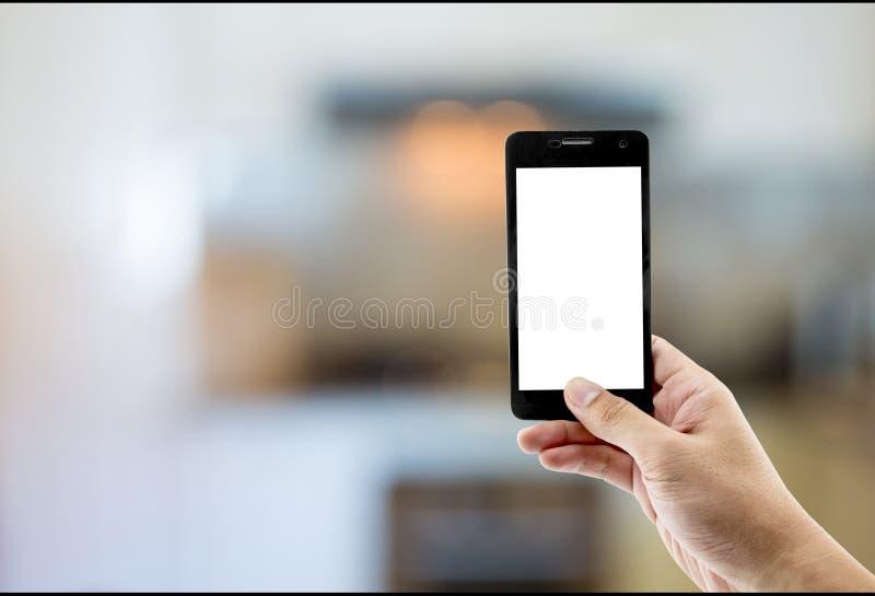 el teléfono del control de la mano toma el sitio de la cocina de la foto imagen de archivo