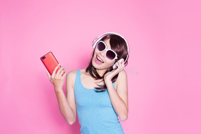 El teléfono del uso de la mujer escucha música fotos de archivo libres de regalías
