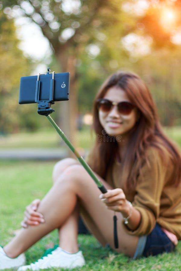 El teléfono elegante del uso del monopod del control de las mujeres toma el selfie de la fotografía en parque imágenes de archivo libres de regalías