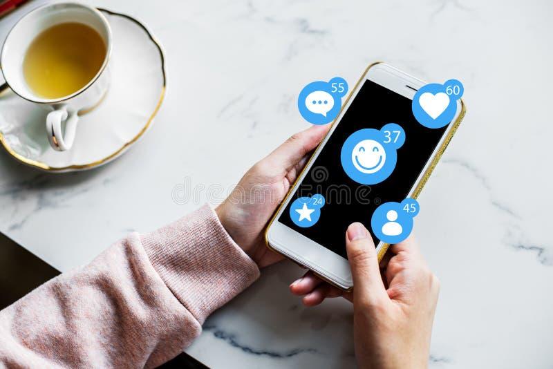 El teléfono elegante en las manos del ser humano con los iconos sociales de la red imágenes de archivo libres de regalías