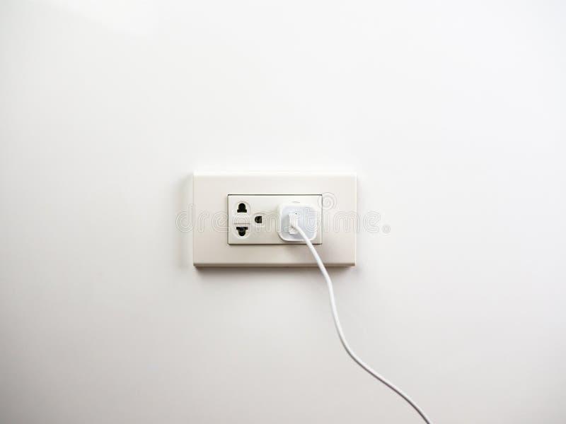 El teléfono enchufó en la pared del zócalo, cargando fotografía de archivo libre de regalías