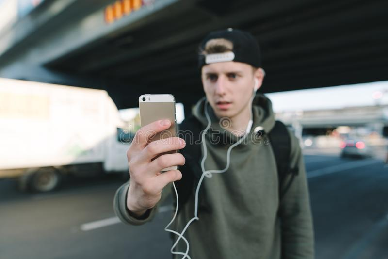 El teléfono está en foco en el fondo de un hombre joven borroso en auriculares y paisaje urbano El estudiante cambia música en el foto de archivo libre de regalías