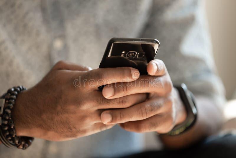 El teléfono móvil africano de la tenencia del hombre usando usos, se cierra encima de la visión imagenes de archivo