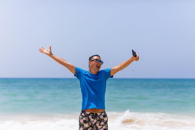 El teléfono móvil del control del hombre joven toma la imagen de la opinión panorámica del mar de la playa del verano foto de archivo libre de regalías