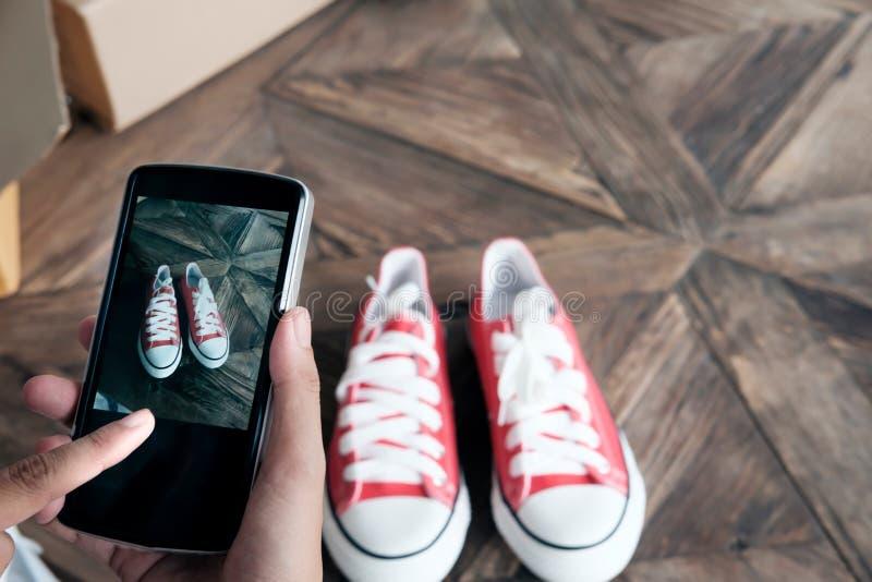 El teléfono móvil del uso en línea del vendedor toma una foto del producto para el uploa fotografía de archivo libre de regalías