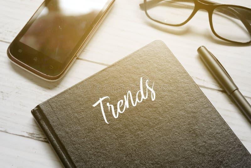El teléfono móvil, las lentes, la pluma y el cuaderno escritos con TENDENCIAS en el fondo de madera blanco con el sol señalan por imagen de archivo libre de regalías