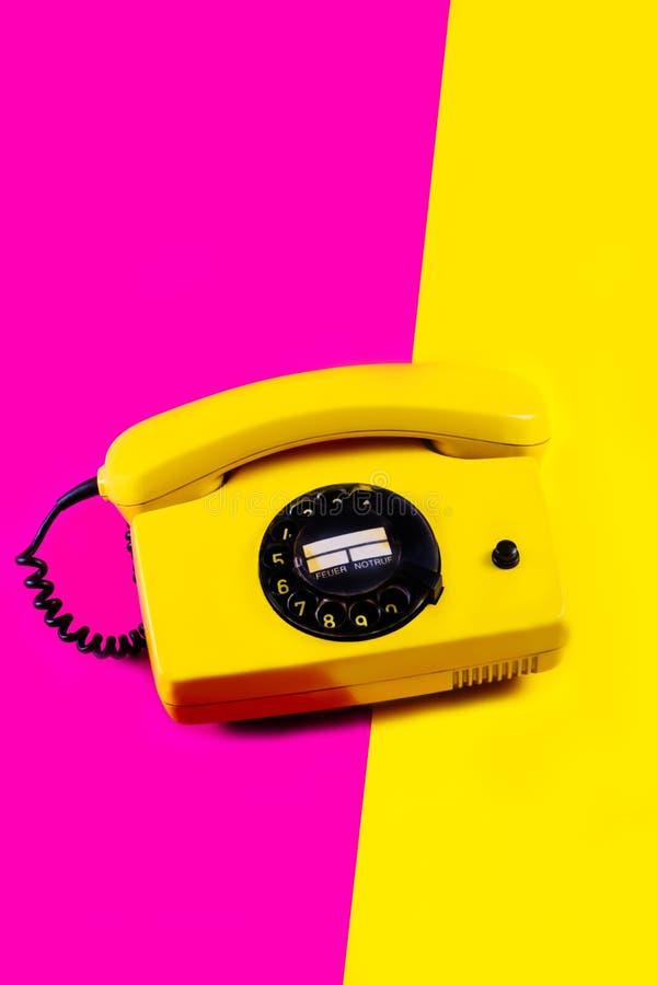El tel?fono retro del vintage fij? a mano la sombra anaranjada pl?stica p?rpura rosada amarilla 90 del viejo estilo del fondo del foto de archivo libre de regalías