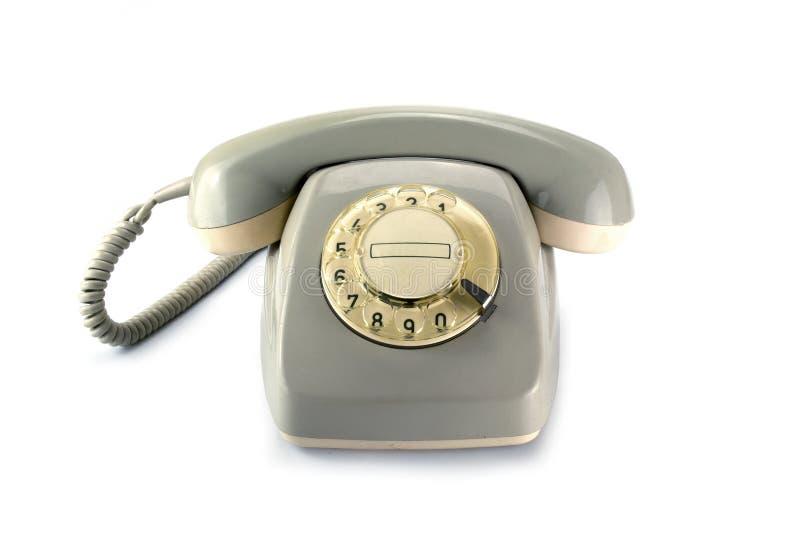 El teléfono rotatorio del vintage, gris amarilleó el plástico en un backgrou blanco fotos de archivo libres de regalías