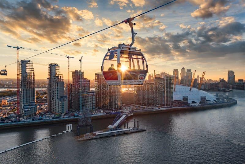 El teleférico de la línea aérea de los emiratos cruza el Támesis de Londres durante puesta del sol fotos de archivo