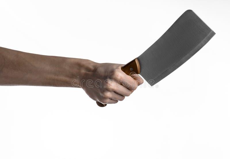 El tema de la cocina: Mano del cocinero que sostiene un cuchillo de cocina grande para cortar la carne en un fondo blanco aislado fotos de archivo libres de regalías