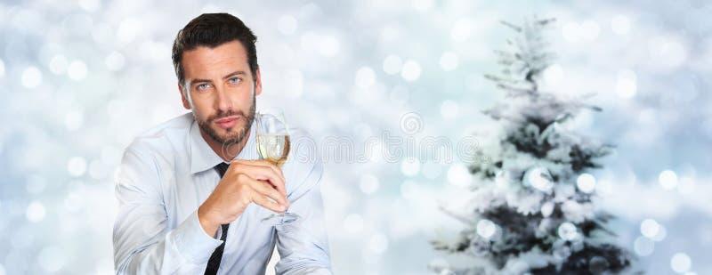 El tema de la Navidad, hombre bebe un vidrio de vino espumoso en empañado imagenes de archivo