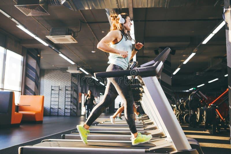 El tema es deporte y música Una mujer inflada hermosa corre en el gimnasio en una rueda de ardilla En su cabeza son los auricular foto de archivo