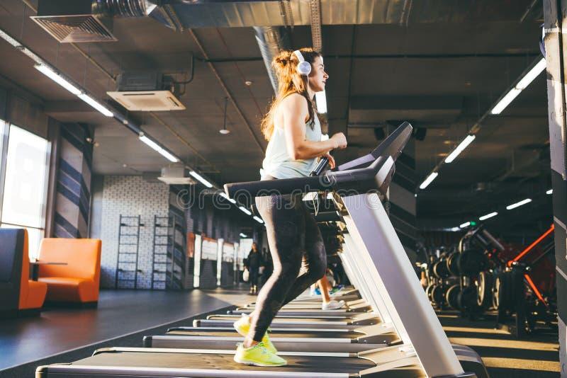 El tema es deporte y música Una mujer inflada hermosa corre en el gimnasio en una rueda de ardilla En su cabeza son los auricular fotografía de archivo
