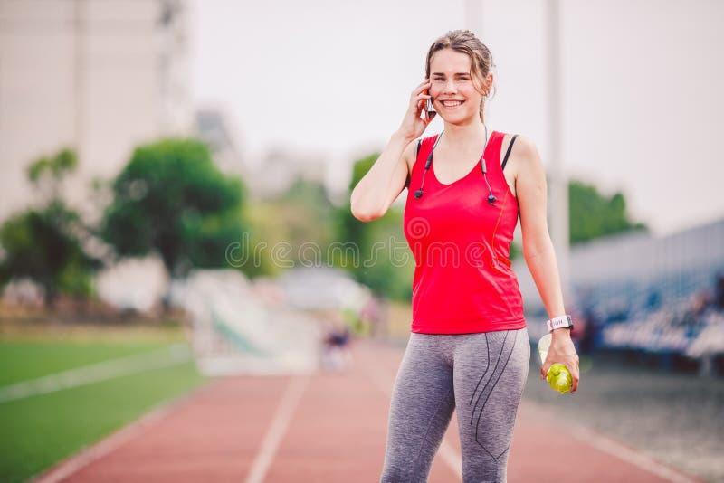 El tema es deporte y salud Una mujer caucásica joven en el entrenamiento en ropa de deportes está hablando usando un teléfono móv fotos de archivo