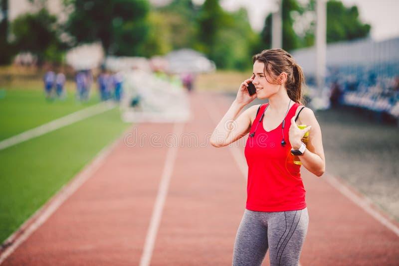 El tema es deporte y salud Una mujer cauc?sica joven en el entrenamiento en ropa de deportes est? hablando usando un tel?fono m?v fotos de archivo libres de regalías