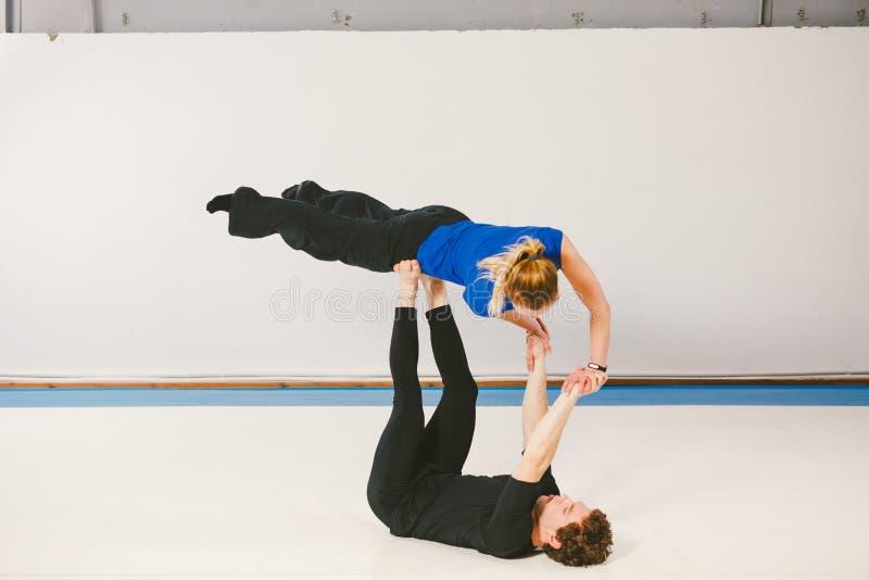El tema es deportes y área cultivada Un varón caucásico joven y un par femenino que practican yoga acrobática en un gimnasio blan fotografía de archivo