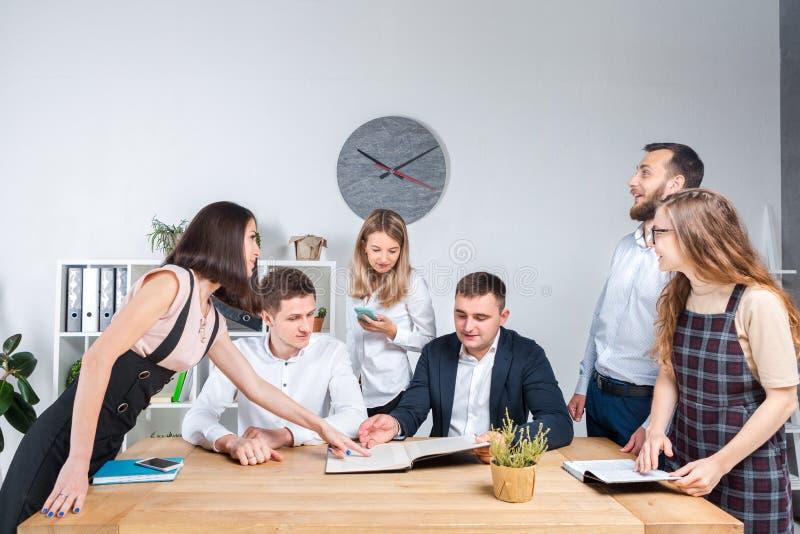 El tema es negocio y trabajo en equipo Un grupo de oficinistas caucásicos jovenes de la gente que celebran una reunión, informe,  imagen de archivo