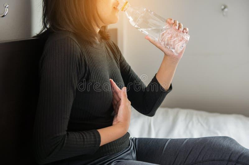 El tener potable del agua de la mujer asiática o ácidos sintomáticos del reflujo fotos de archivo
