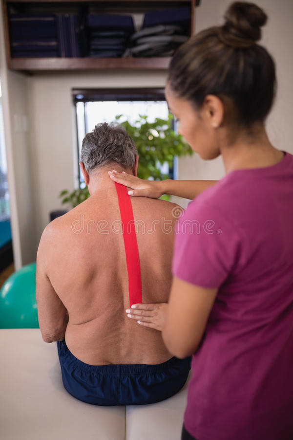 El terapeuta de sexo femenino que aplica la cinta terapéutica elástico encendido apoya de paciente masculino mayor descamisado fotos de archivo
