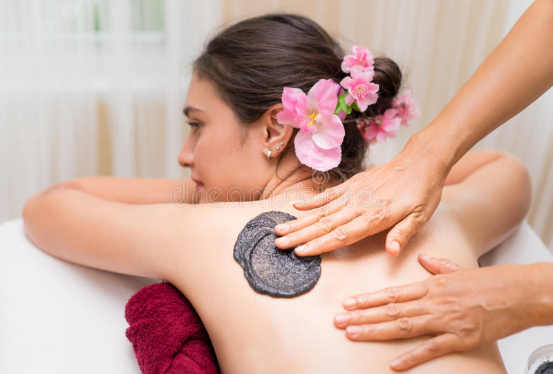 El terapeuta del masaje del balneario está fregando el carbón de leña caliente negro imágenes de archivo libres de regalías