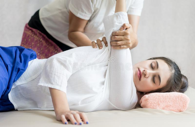 El terapeuta tailandés del balneario de Massuer es masaje que estira un brazo de la mujer imágenes de archivo libres de regalías