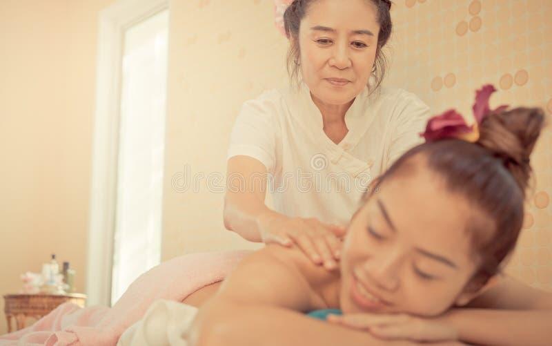 El terapeuta tailandés del balneario es bondadoso dando masajes a la parte posterior de la mujer imagen de archivo libre de regalías