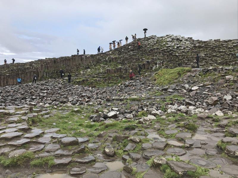 El terraplén del gigante de Visitng de los turistas en Irlanda del Norte en un día lluvioso foto de archivo libre de regalías