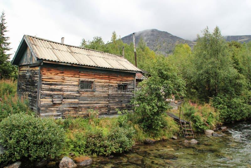 El territorio al lado del centro de ocio Cuelporr en las montañas del Khibiny Choza de madera cerca del río de la montaña foto de archivo libre de regalías