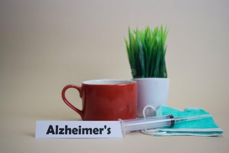 El texto de Alzheimer, pote de la hierba, taza de café, jeringuilla, y máscara verde de la cara imagen de archivo