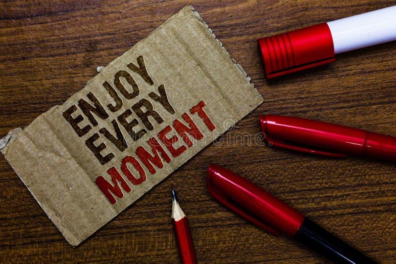 El texto de la escritura de la palabra disfruta de cada momento El concepto del negocio para estar satisfecha con su vida tiene v imágenes de archivo libres de regalías