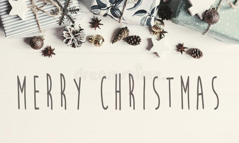 El texto de la Feliz Navidad en plano moderno de la Navidad pone con los ornamentos imagen de archivo libre de regalías