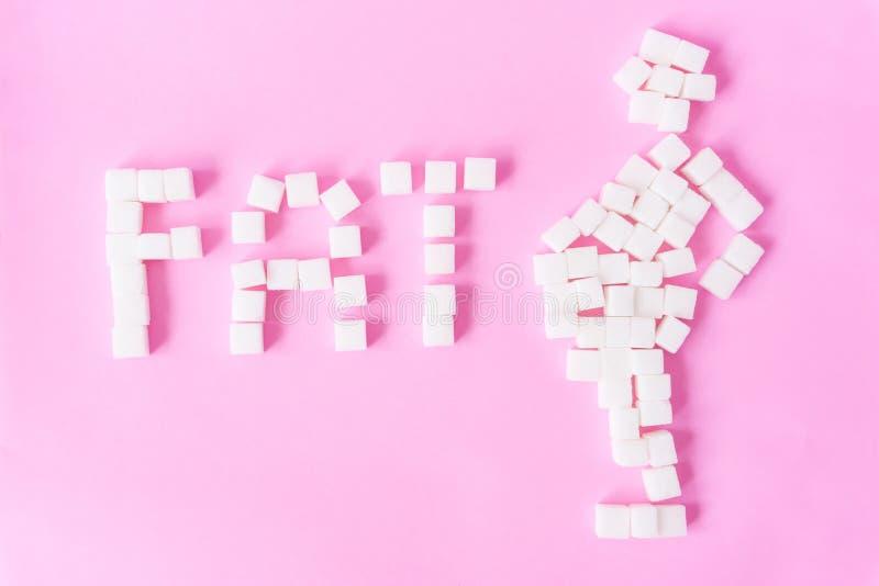 El texto del FAT y el hombre gordo forman con los cubos del azúcar en backgr rosado dulce imagen de archivo libre de regalías